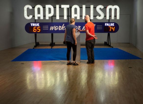 "Annie Krempa and Patrick Bradley look at Steve Lambert's ArtPrize entry ""Capitalism Works For Me"" at Kendall College of Art and Design in Grand Rapids Tuesday, Sept. 23, 2014. ""I like that it's interactive,"" said Krempa about the entry. Krempa and Bradley are from Traverse City. (Cory Morse 
