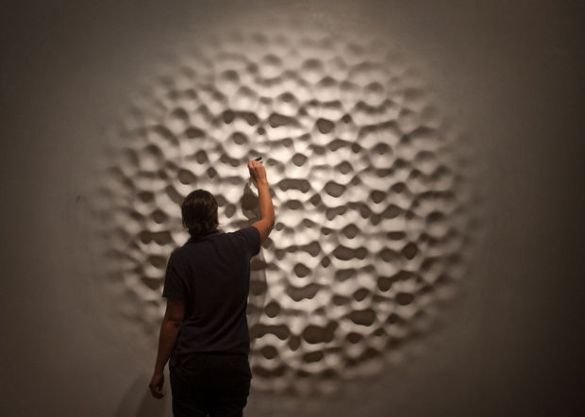 Loris Cecchini's 'Wallwave Vibration' is one of the sixteen works featured in Meijer Gardens' ArtPrize exhibition, 'Highly Recommended: Emerging Sculptors.' Carrie Westra of the Meijer Gardens staff applies paint Tuesday, September 16, 2014. (Chris Clark | MLive.com)